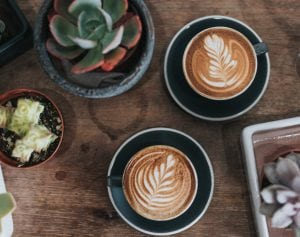 Image of two coffees and a plant
